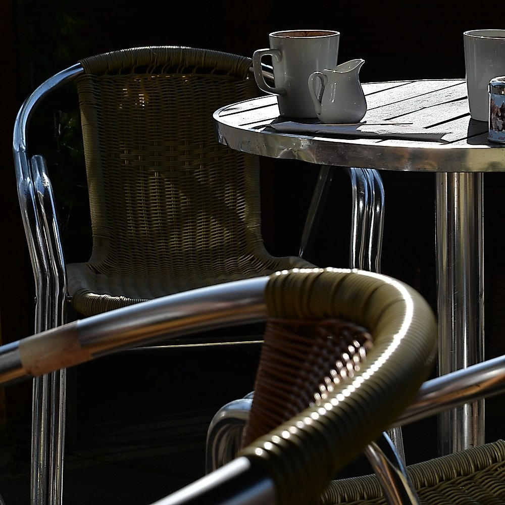 Colour photo of empty cafe chairs  and used cups