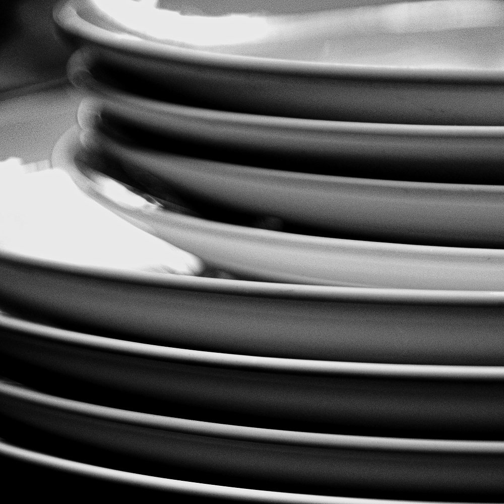 Black and white photo - a stack of plates